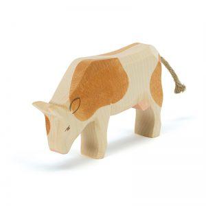 Figura legno mucca pezzata marrone che mangia- Ostheimer
